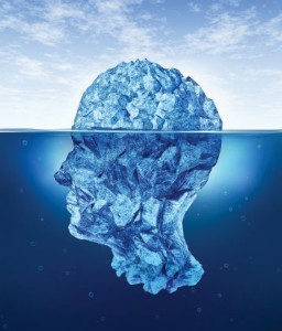 Human brain risks with an iceberg in the shape of a head partialy submerged in the cold arctic ocean as a health care medical symbol for hidden neurological and psychological symptoms.